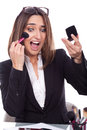 Businesswoman retouches her makeup in the office Stock Image