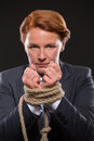 Businesswoman s hands tied up with rope portrait of in red hair looking at the camera corageous glance Royalty Free Stock Image