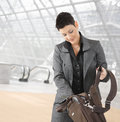 Businesswoman searching in laptop bag Stock Images