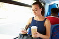 Businesswoman sending text message on bus whilst holding takeaway coffee Stock Image