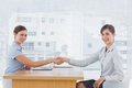 Businesswoman shaking hands with interviewee and both smiling at camera desk in office Stock Photography