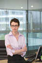 Businesswoman, with short hair and spectacles, leaning against desk in office, arms folded, portrait Royalty Free Stock Photo