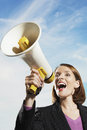 Businesswoman shouting through megaphone smiling against blue sky Royalty Free Stock Photos