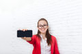Businesswoman show cell smart phone screen with empty copy space wear red jacket glasses happy smile Royalty Free Stock Photo