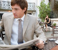 Businesswoman sitting coffee shop terrace having mobile cell phone conversation businessman sits reading newspaper classic city Stock Image