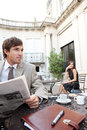 Businesswoman sitting coffee shop terrace having mobile cell phone conversation businessman sits reading newspaper classic city Stock Photo