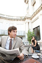 Businesswoman sitting coffee shop terrace having mobile cell phone conversation businessman sits reading newspaper classic city Royalty Free Stock Images