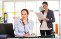 Businesswoman sitting at her desk with colleague Royalty Free Stock Photo