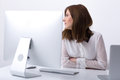 Businesswoman sitting at her workplace in office pensive Royalty Free Stock Photography