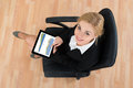 Businesswoman Sitting On Office Chair With Digital Tablet Royalty Free Stock Photo