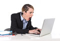 Businesswoman sitting at office desk working with laptop in stress looking upset attractive white blond and dealing work issues Stock Image