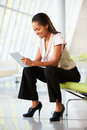Businesswoman Sitting On Sofa In Office Using Digital Tablet Royalty Free Stock Images