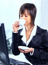 Businesswoman sitting at the table in office lobby drinking coffee Royalty Free Stock Photo
