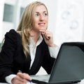 Businesswoman sitting thinking at her desk in front of her laptop computer and staring into the distance Stock Photography