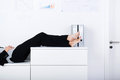 Businesswoman sleeping side view of legs on counter in office Stock Image