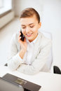 Businesswoman with smartphone in office business and communication smiling Royalty Free Stock Image
