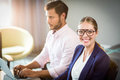 Businesswoman smiling at camera while her colleague using laptop Royalty Free Stock Photo