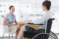 Businesswoman speaking with disabled colleague at desk in office Stock Photos