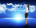 Businesswoman standing against blue landscape with Royalty Free Stock Photo