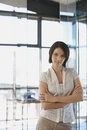 Businesswoman standing arms crossed in office portrait of beautiful young Royalty Free Stock Photography