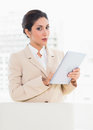 Businesswoman standing behind her chair holding digital tablet in office Royalty Free Stock Photo