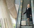 Businesswoman standing on escalator with luggage portrait of a Stock Images