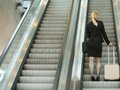 Businesswoman standing on escalator with travel bags portrait of a rear view Royalty Free Stock Images