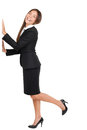 Businesswoman standing on one leg with hands on wall full length portrait of happy young isolated over white background Stock Photography