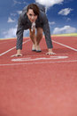 Businesswoman on start line of a running track Royalty Free Stock Photo