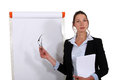 Businesswoman stood by flip chart in front of Royalty Free Stock Photo