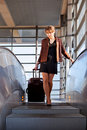 Businesswoman with suitcase on the  escalator Stock Photos