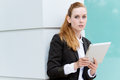 Businesswoman with tablet pc serious redhead looking in camera Stock Image