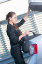 Businesswoman takes bag out from the car her laptop Stock Images