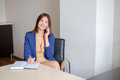 Businesswoman taking mobile phone call and writing notes into calendar at office desk. Royalty Free Stock Photo