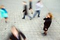 Businesswoman talking on mobile phone young attractive motion blurred commuters walking to work Royalty Free Stock Photos