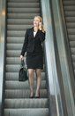 Businesswoman talking on phone on escalator portrait of a Stock Photography