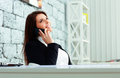Businesswoman talking on the phone and looking up at copyspace young happy in office Royalty Free Stock Image