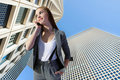 Businesswoman talking on phone on urban background Royalty Free Stock Images