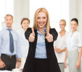 Businesswoman with thumbs up in office Royalty Free Stock Photo