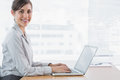 Businesswoman typing on her laptop at desk and smiling at camera in office Royalty Free Stock Photography