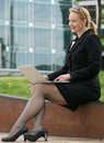 Businesswoman typing on laptop outdoors in the cit portrait of a city Royalty Free Stock Photos