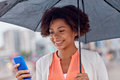 Businesswoman with umbrella texting on smartphone Royalty Free Stock Photo