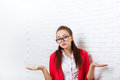 Businesswoman unsure gesture wear red jacket glasses confused shrug shoulders business woman over office wall Stock Photography