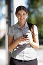 Businesswoman using cell phone portrait of pretty smiling Royalty Free Stock Photo