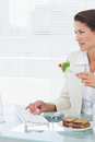 Businesswoman using computer while eating salad at desk Stock Image