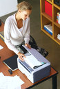 A businesswoman using copier machine pretty young at the office Stock Image