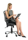 Businesswoman using digital tablet while sitting on office chair full length of young against white background Stock Images