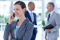 Businesswoman using her phone with two colleague behind her at the office Stock Photo