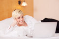 Businesswoman using laptop while lying on bed happy Royalty Free Stock Photo