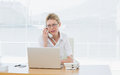 Businesswoman using laptop and phone at desk Royalty Free Stock Photo